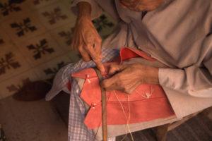 Vendedor de babuchas en Marrakech cosiendo